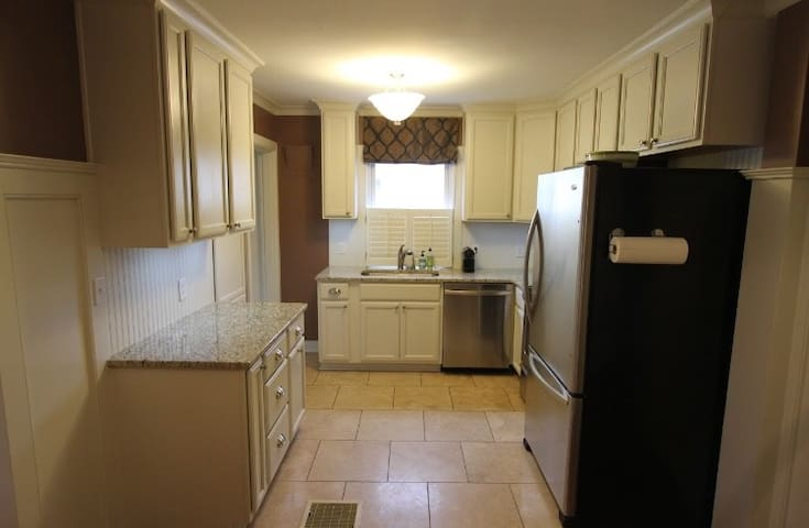Fully equipped kitchen with stainless steel appliances, granite countertops, Nespresso machine, French press coffee maker, and instant hot water dispenser