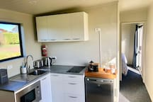 Kitchenette with stove top, microwave oven and fridge.