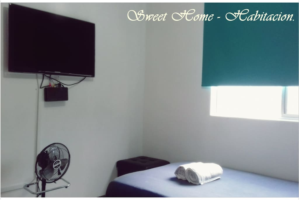 Habitación con TV, ventilador, silla y toallas.