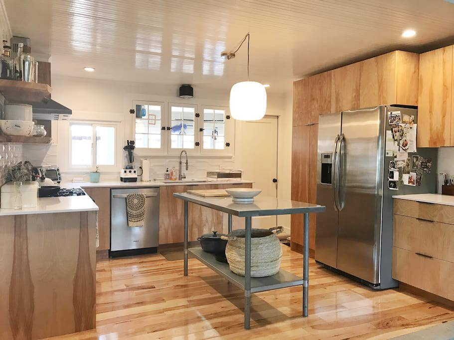 Open and bright newly remodeled kitchen with a dishwasher, gas range and oven, toaster oven and large refrigerator. The door in the back corner leads to the mudroom on the back side of the house. Access the deck through this door.