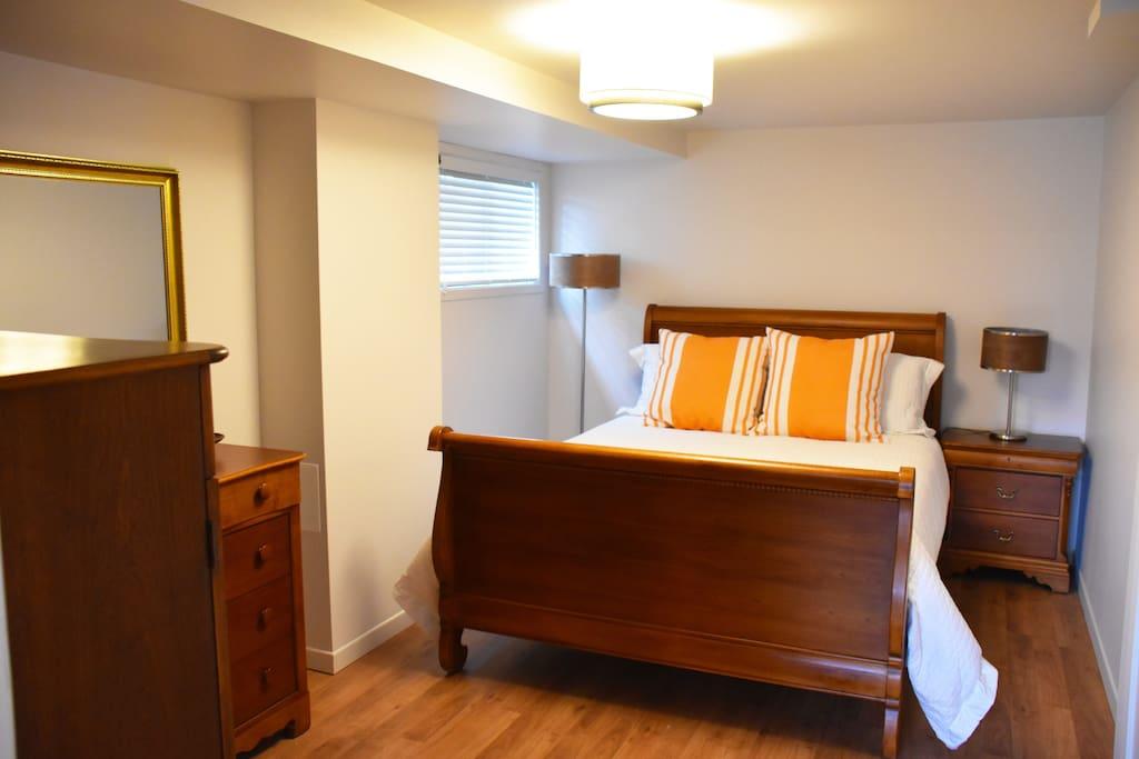 Chambre lit Queen avec deuxième télévision.