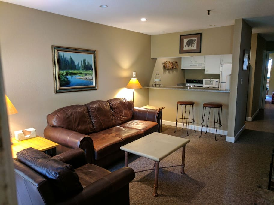 The living room has a leather couch and chair with a fire place.