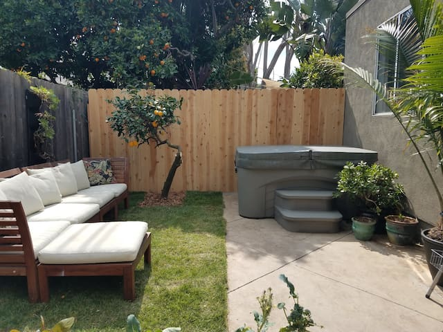 Private backyard with jacuzzi, sectional couch, bbq, and herb garden.