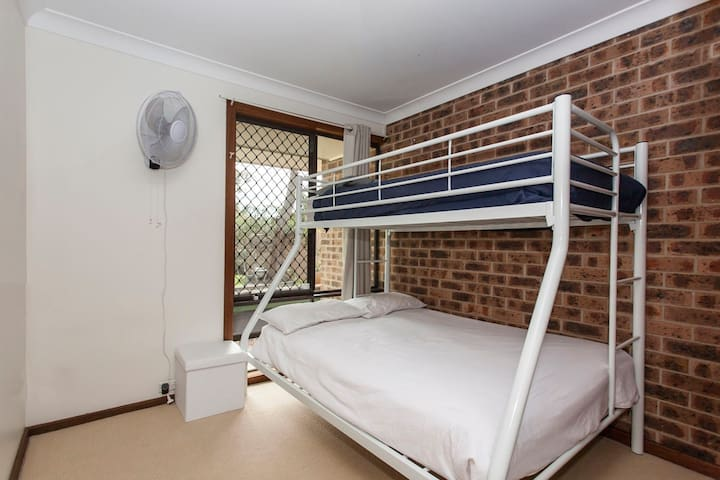 Bedroom 3 with comfortable triple bunk and wall fan.
