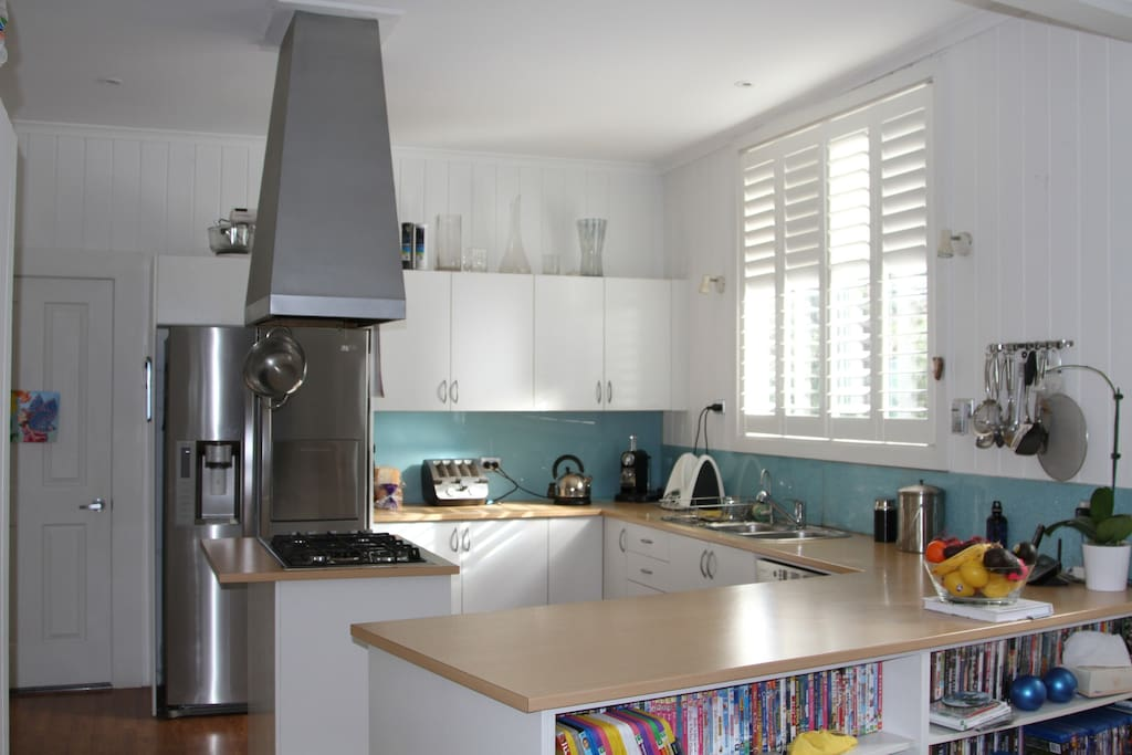 Kitchen with modern appliances opening to family room, lounge and large flat screen TV