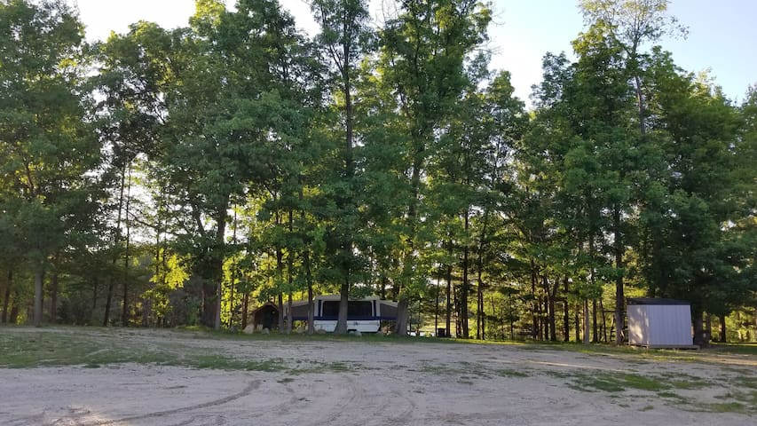 Parking area beside pop-up camper and woodshed on the right for fire pit.