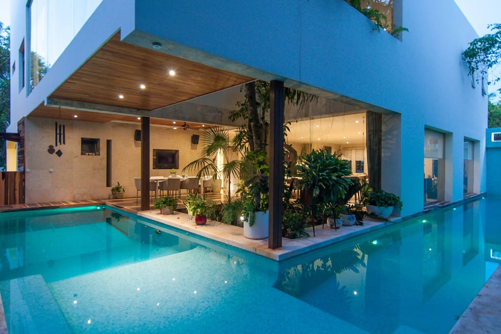 Casa Morgana boasts a large backyard complete with wrap-around pool, outdoor dining patio (with TV), multi-level grilling space, and a fish pond.
