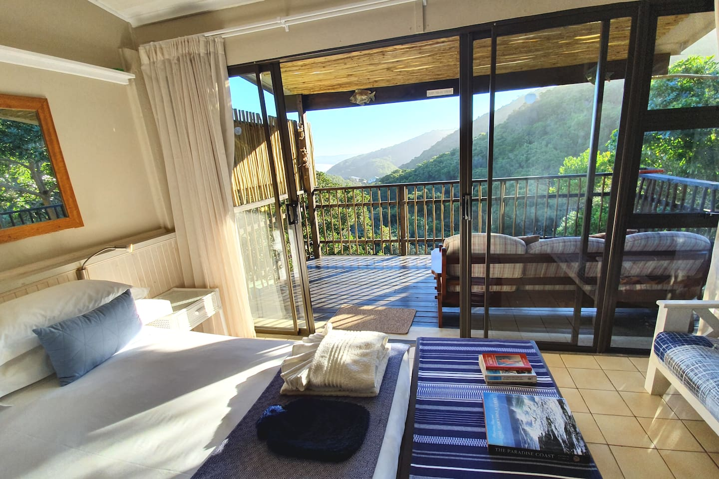 Main bedroom with queen bed and private balcony with  sea and forest views.