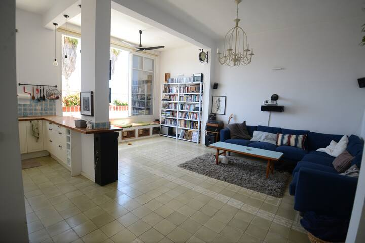 Spacious, light filled living room with attached kitchen. Additional dining table is not pictured.