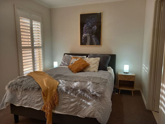 Bedroom 1, queen bed, semi-ensuite, built in robe, plantation shutters and sunblinds and ceiling fan.
