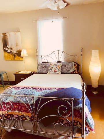 Queen bed in studio area.