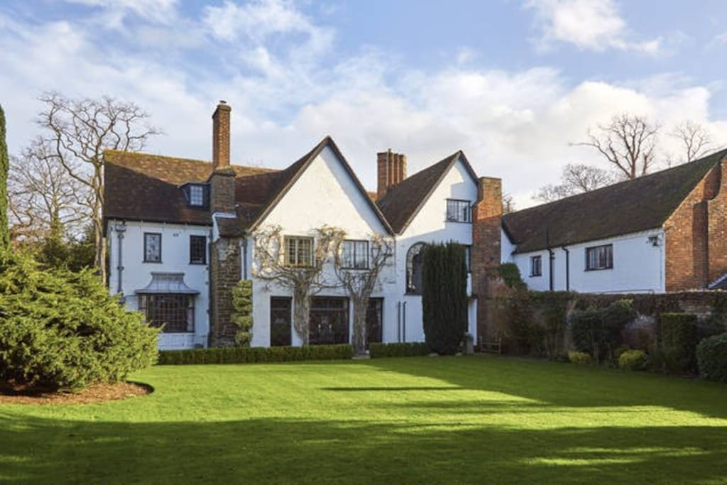 The West front of Harlington Manor. In Spring the wisteria is a perfumed riot of colour. The Garden Bedroom's two windows are those surrounded by the wisteria.