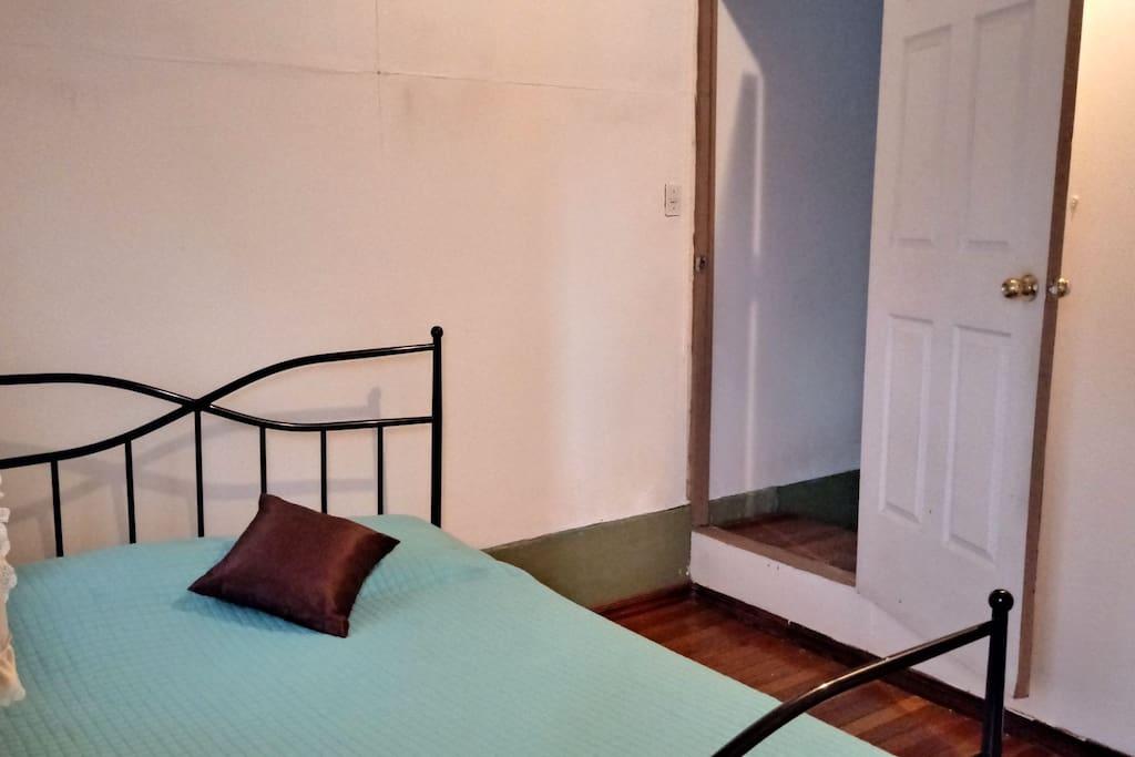 El dormitorio y detrás de la puerta una pequeña sala de T.V.