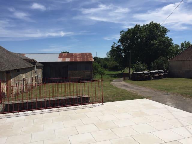 La terrasse donnant sur les dépendances agricoles et la campagne environnante