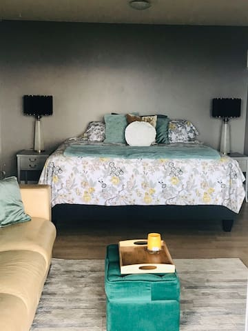 Master bedroom from sliding patio door.   Comfy leather sofa to curl up on & watch the sunsets.   Fireplace (electric) for those chilly nights or just a little ambience.