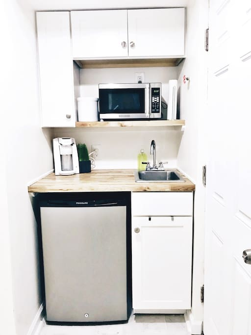 Private kitchenette in the basement with refrigerator, freezer, microwave, coffee maker, and full sets of dishes, glasses, and silverware for exclusive guest use.