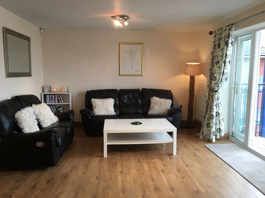 """Sitting room: digital Free View 42"""" TV, DVD player, 3 and 2 seater sofas, French doors leading to balcony"""