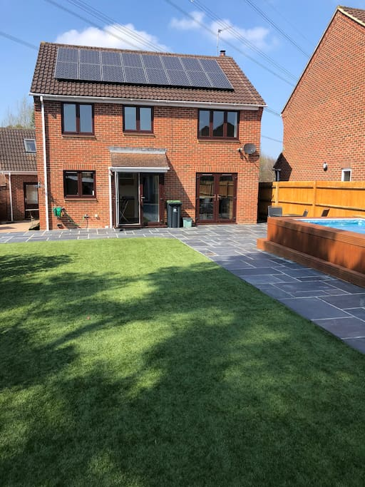 Large back garden with artificial grass and heated pool