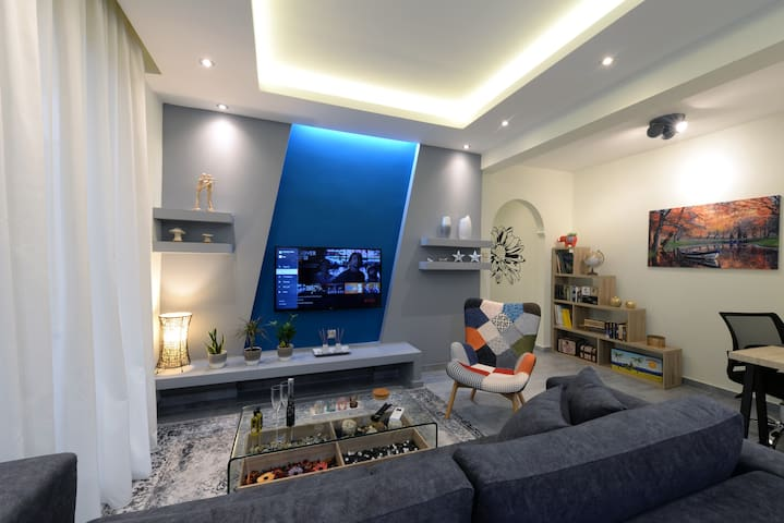 """The living Room, the place to relax.   42"""" TV with Netflix Access.  Fully air-conditioned. Strong Wifi internet Access. Selection of Books, Comics & Journals in Greek and English language.  Sofa can be turned in big double bed."""