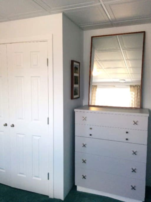 Closet, dresser, and mirror in bedroom