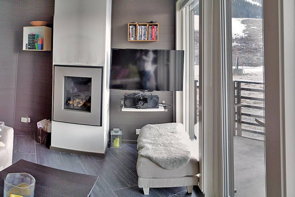 Stue med to store tosetersofaer, gasspeis, TV med kabel-tv og utgang til terrasse.