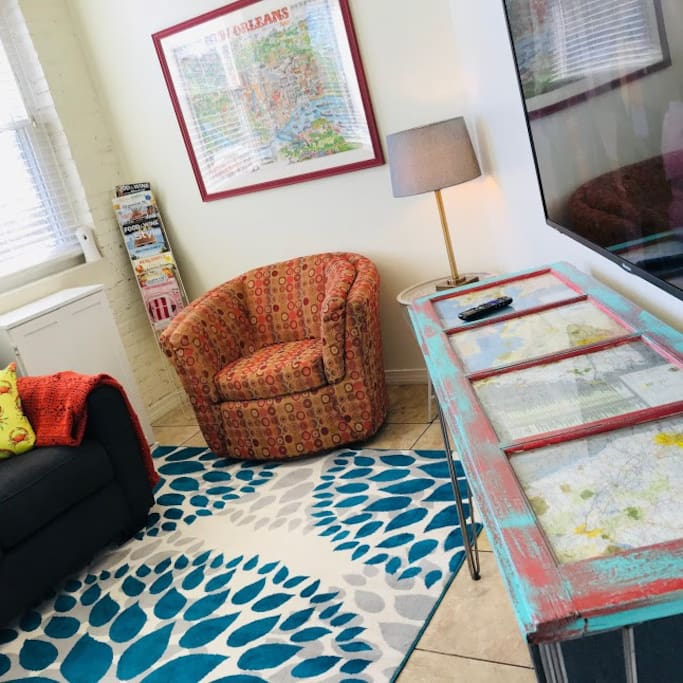 The living area includes handmade furnishings and artwork, Louisiana themed vintage maps and decor.