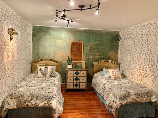bedroom 2 - twin beds with original wall