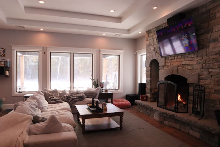 Main living room downstairs. Low to the ground cloud couch, curved LG tv with 5.1 surround sound, and fire place.