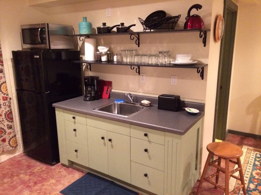 Min-kitchen with fridge, microwave, sink, hot plate, toaster, coffee maker, dishes, and utensils.