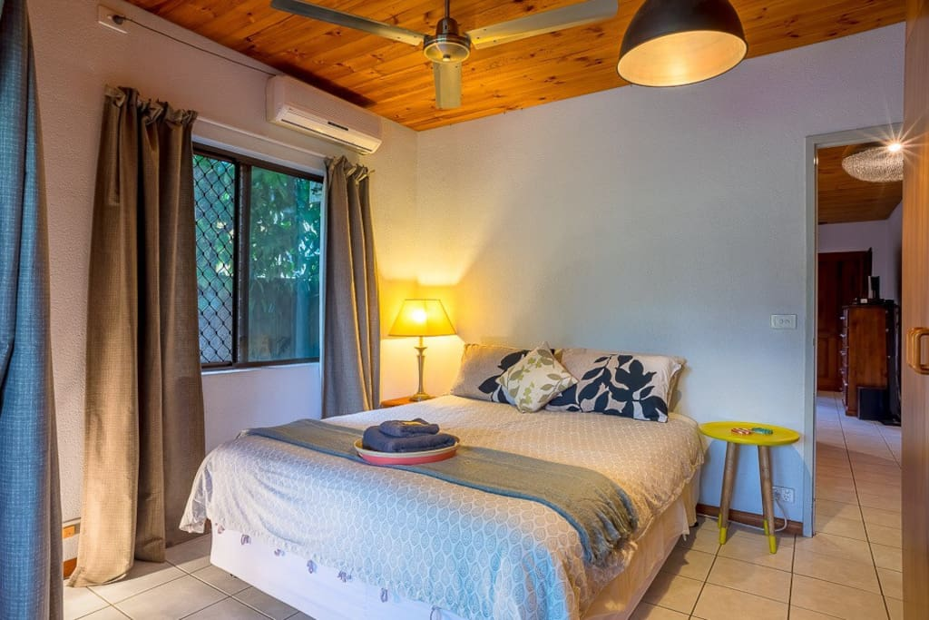 Comfortable queen size bed in cozy room with blackout curtains and air conditioning.