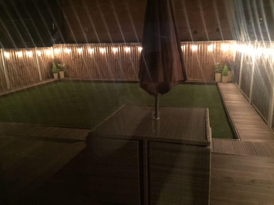 Fully illuminated & landscaped rear garden is ideal for relaxing day or night, 8 seater rattan patio set including 2 sun loungers & heater.