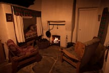 Evening shot of the living area, open turf fire and kitchen bed.