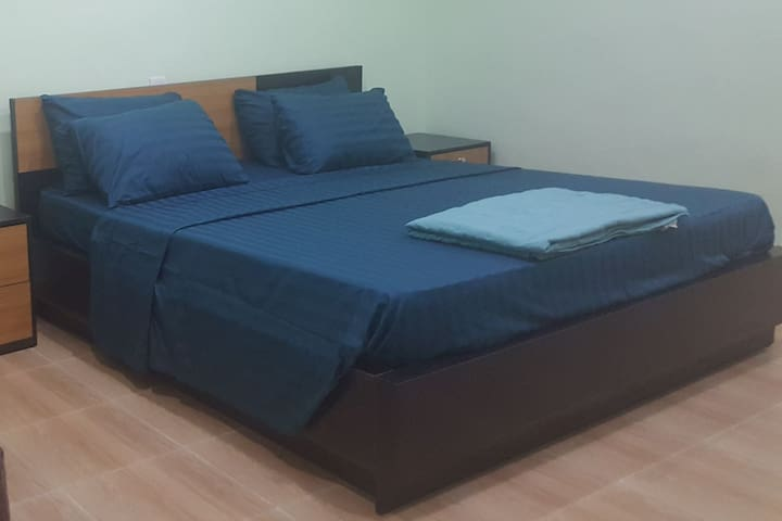 Green room with king size bed and  1 twin bunk