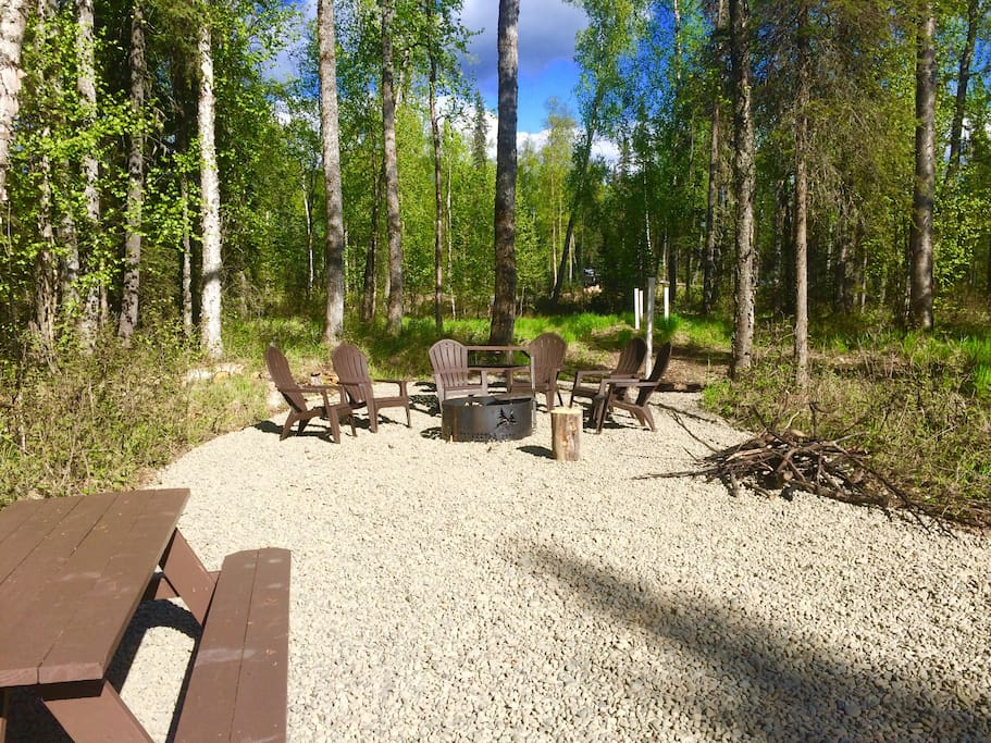 Gorgeous outside area with 6 chairs, and amazing fire ring, 2 picnic tables, firewood, large area for kids to explore