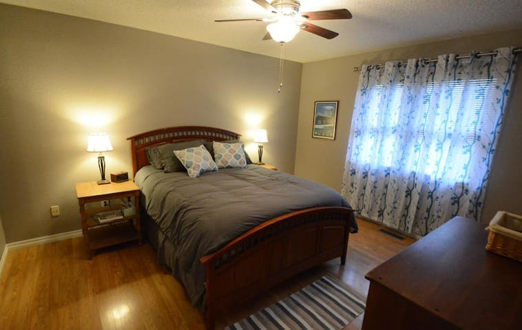 The master bedroom features a queen bed, nightstands with reading lamps, ceiling fan, and a full dresser