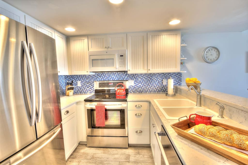 Bright beachy blue glass backsplash gives a fun pop of color to the room!
