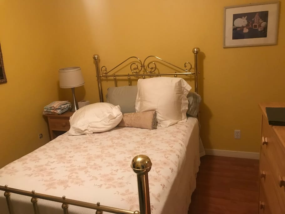 Yellow guest room with full size bed. Shares bathroom with Blue guest room.
