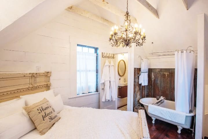 Our barndominum's bedroom upstairs offers a queen vintage bed, a clawfoot tub and shower combination open to the bedroom and a small private toilet room.  There is a towel-warmer on wall. Robes and slippers are provided!