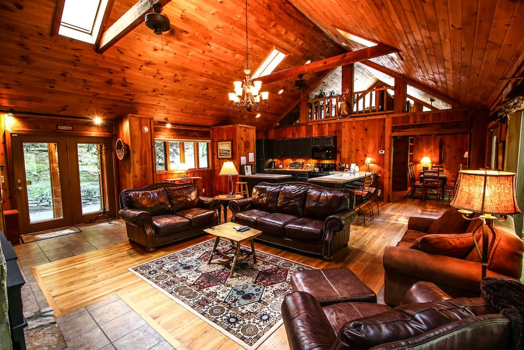 The living area mirrors the woodland setting, with beamed ceiling and comfortable couches and seating for the whole family.