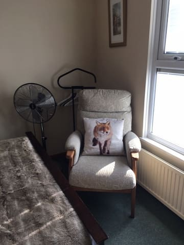 Rotating fan, gentleman's dresser with hangers and comfortable chair