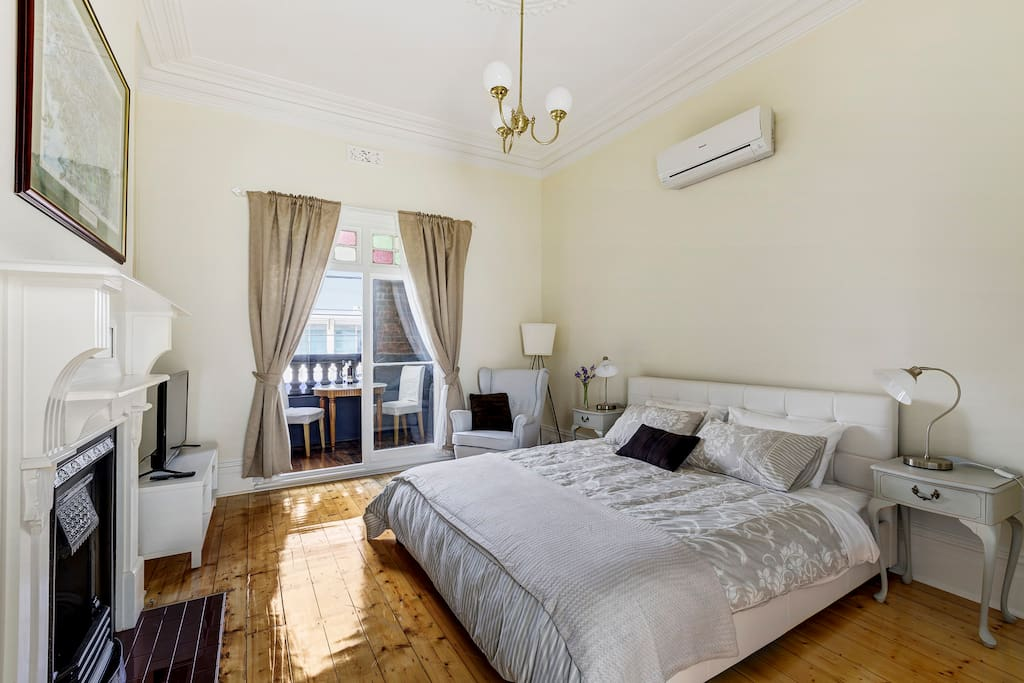 Room #1 huge room with comfy king bed, TV, lovely balcony overlooking Sydney Road, your own heating and air conditioning and a convenient cupboard for clothes with ironing board and iron.