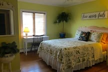 The front bedroom is sunny and spacious offering a Queen, wicker desk, large closets, comfy chair, ceiling fan, air conditioner and a private half bath within the room.
