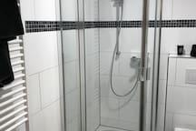 Badezimmer mit Dusche, Toilette und Waschbecken