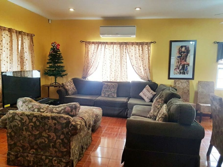 Comfy, cozy living room, complete with large flat screen TV.