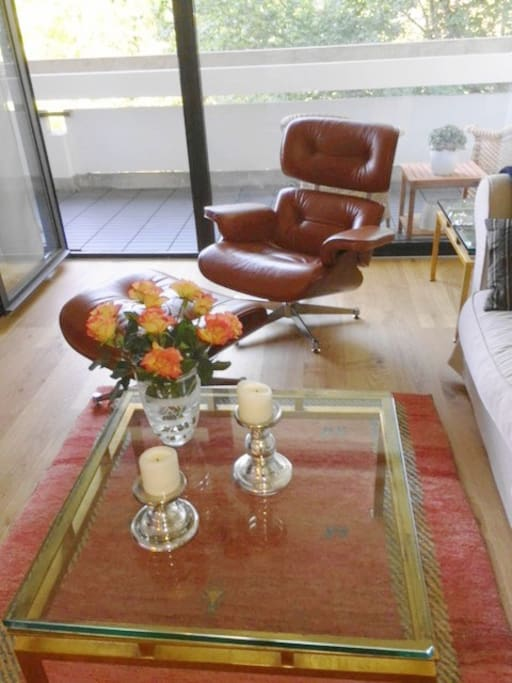 The living room comprises a comfy armchair as well as a couch that are next to the big glass door, which leads to the 1st balcony.