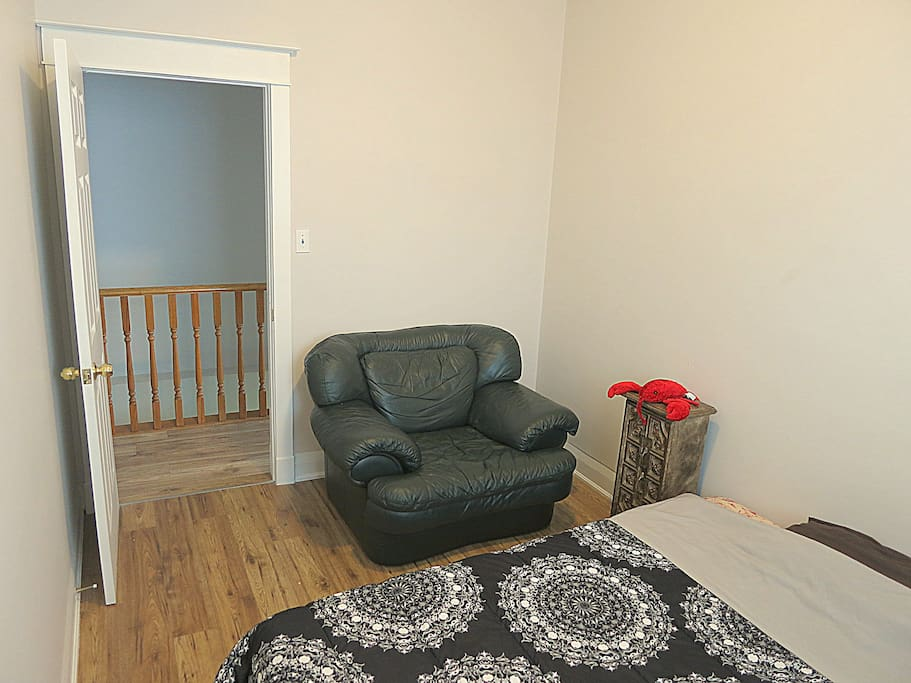 The bedroom features a real queen bed and a real leather arm chair.