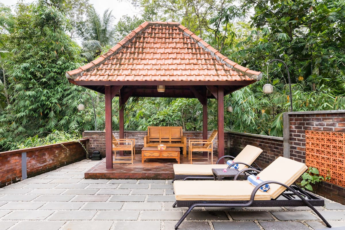 Relax under the Stylish Pergola at a Serene Poolside Villa