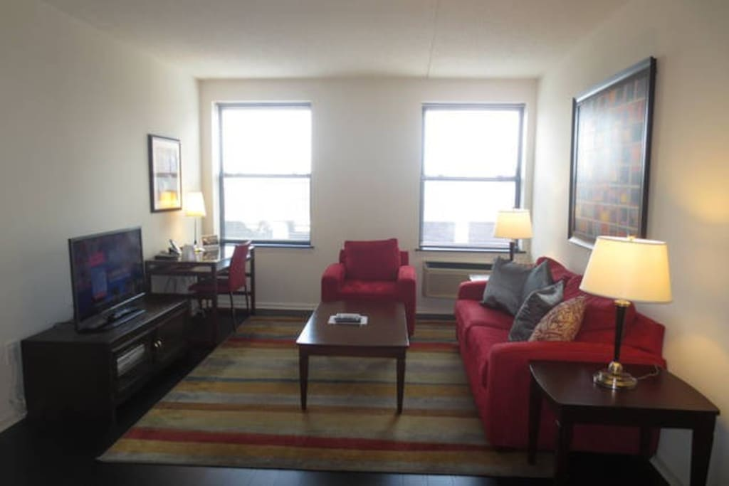 Spacious living room with entertainment center and convenient work desk with chair, lamp and WiFi