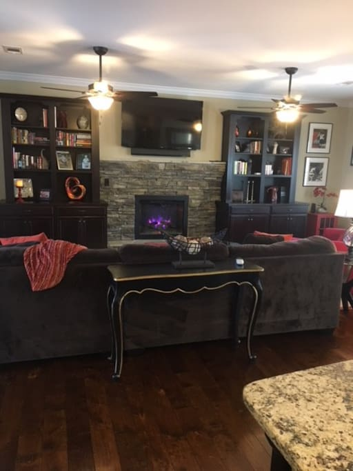 Spacious living room area, with open floor plan. The living room has a love seat that turns into a pull out twin bed.  This room is perfect for watching tv and hanging out by the fireplace.