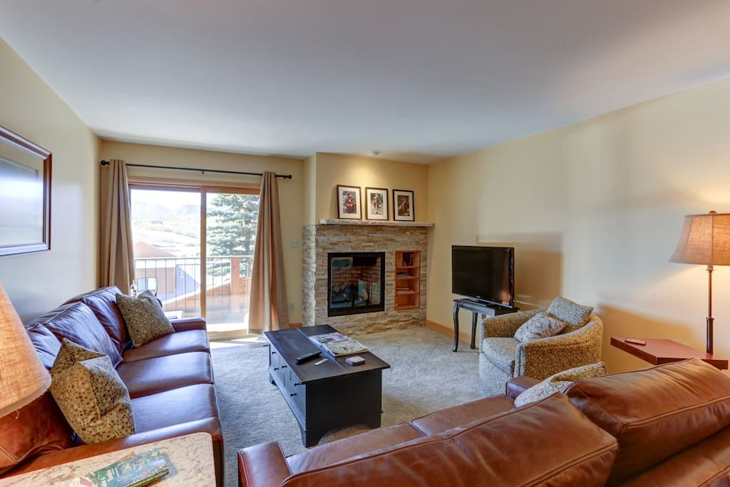 Living room with brand new leather couches, gas fireplace, etc.